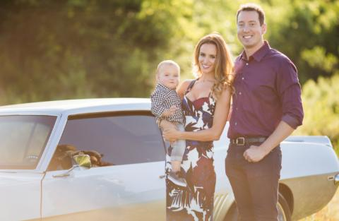 kyle and samantha busch next to muscle car holding child